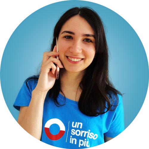 Volontaria di Un Sorriso in Più sorridente al telefono